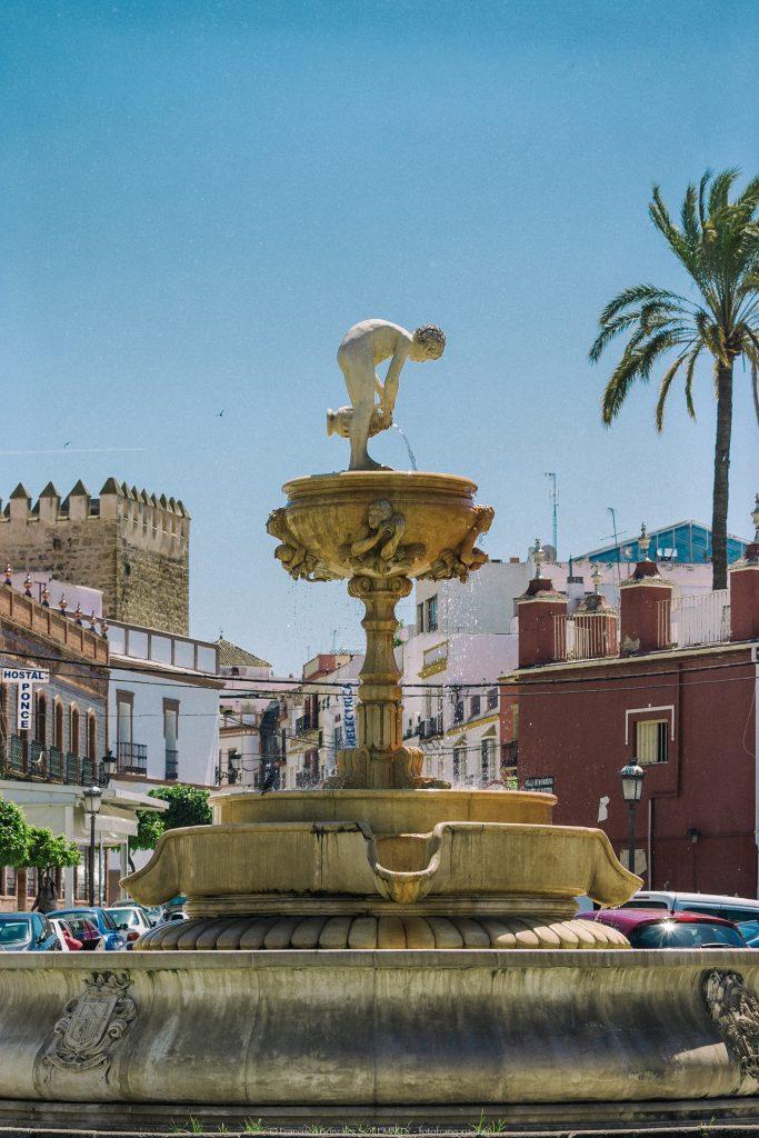 Fuente con la escultura de un niño vertiendo agua con muralla árabe al fondo y palmera